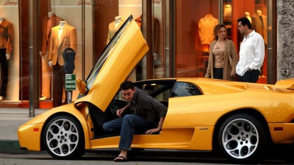 Young adult, millennial stepping out of Lamborghini, wealth