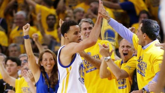 Stephen Curry, number 30 of the Golden State Warriors, celebrates with fans as venture capitalist Bill Gurley grins in the background.