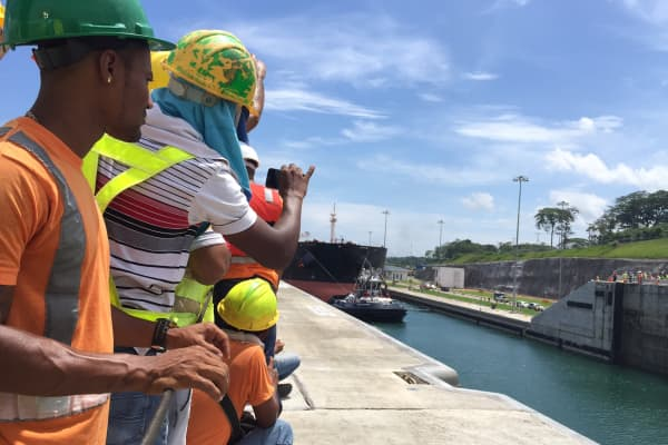 Hundreds of construction workers lined the sides of the new lane of the Panama Canal to watch the first ship, a post-Panamax ship pass through.