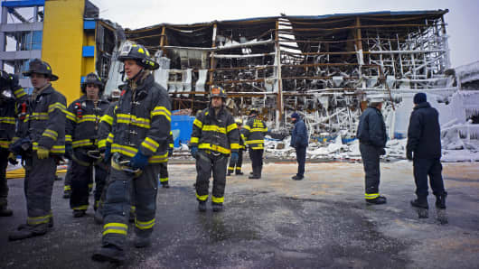 New York City firefighters and others stand near CitiStorage, a paper storage facility in the Williamsburg section of Brooklyn in New York City, Thursday, Feb. 5, 2015.