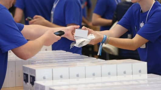 Employees prepare Apple iPhones for sale.