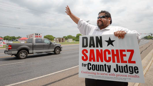 Candidate Dan Sanchez waves at passing vehicles as he campaigns outside of Burns Elementary, May 24, 2016, in Brownsville, Texas.