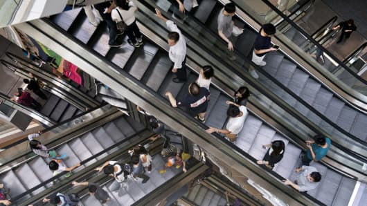 People ride on escalators in a shopping mall in Hong Kong.