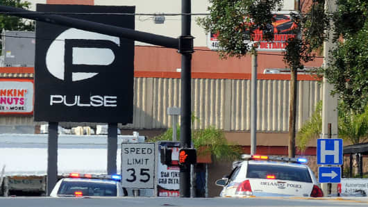 """Orlando police officers seen outside of Pulse nightclub after a fatal shooting and hostage situation on June 12, 2016 in Orlando, Florida. A source close to family said the gunman sent a text message to his wife during the rampage, asking """"do you see what's happening?""""."""