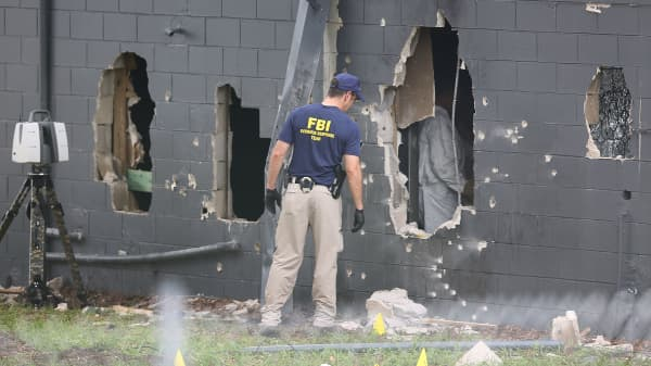 FBI agents investigate the damaged rear wall of the Pulse Nightclub where Omar Mateen allegedly killed at least 50 people on June 12, 2016 in Orlando, Florida.
