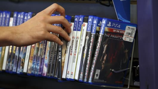A customer selects a Sony Corp. PlayStation 4 (PS4) video game displayed for sale at a GameStop Corp. store in West Hollywood, California.