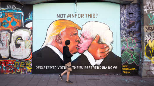 A man passes a mural that has been painted on a derelict building in Stokes Croft showing US presidential hopeful Donald Trump sharing a kiss with former London Mayor Boris Johnson on May 24, 2016 in Bristol, England.