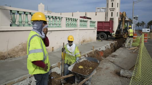 Construction workers make repairs to a street in Old San Juan, Puerto Rico