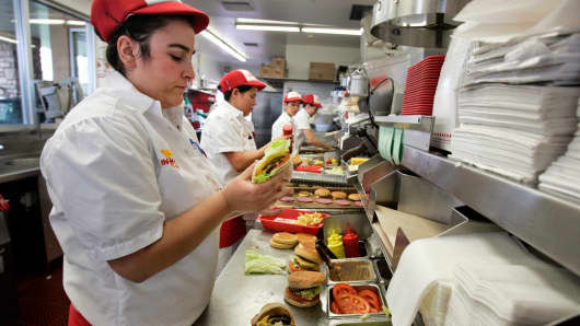 An employee prepares burgers for lunch customers at In-N-Out in San Marcos, California.