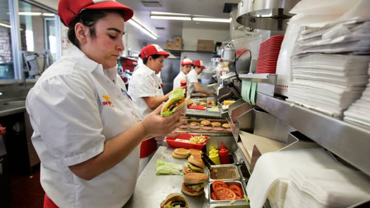 An emploуee prepares burgers for lunch customers at In-N-Out in San Marcos, California.