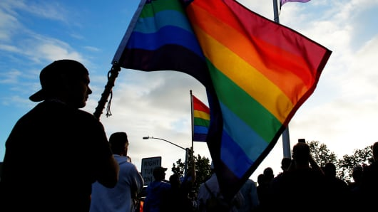 Mourners gather under an LGBT pride flag in San Diego, California, during a candlelight vigil in remembrance for mass shooting victims in Orlando, June 12, 2016.