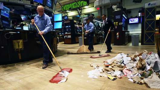 Employees clean up trash on the floor of the New York Stock Exchange.