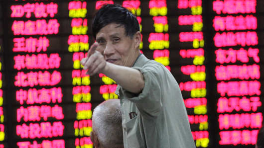 An investor observes stock situation at an exchange hall in Nanjing, Jiangsu Province of China.