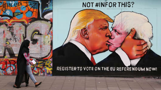 Passer-by views a mural showing Donald Trump (L) kissing the former Mayor of London and Conservative MP, Boris Johnson, in Bristol, England on May 24, 2016.
