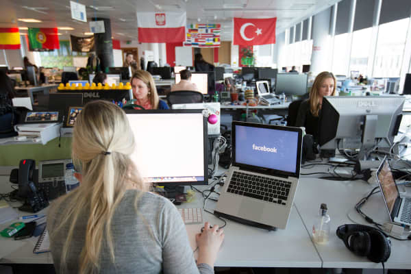 Facebook employees work on their laptops in European headquarters at Hanover Quay in Dublin, Ireland