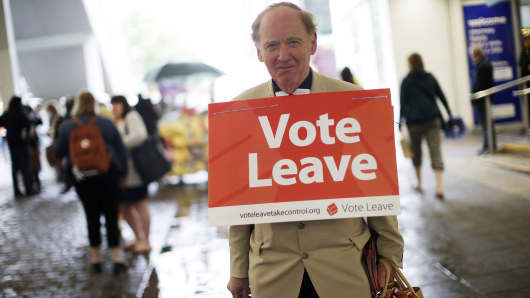 A 'Vote Leave' campaigner wearing a placard around his neck distributes leaflets to members of the public in Manchester, U.K., on Saturday, June 11, 2016. U.K.