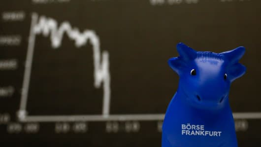 A plastic bull figurine, symbol of the Frankfurt stock exchange is pictured in front of the German share price index DAX board at the Frankfurt stock exchange.