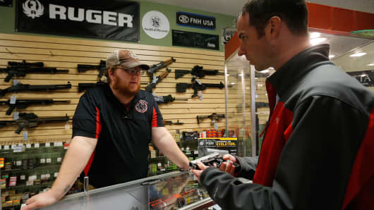 A Metro Shooting Supplies' employee speaks to a customer about the purchase of a 9mm handgun in Bridgeton, Missouri.