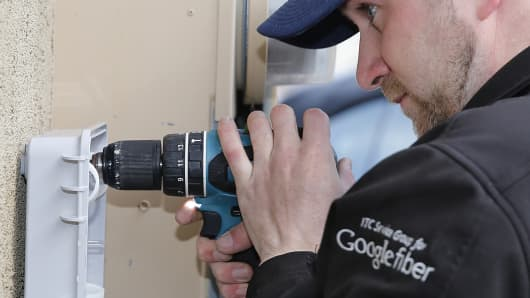 A Google Fiber technician installs a fiber optic box at a residential home as part of Google Fiber services in Provo, Utah. Google Fiber is now be headed to Dallas.