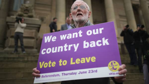 A Vote to Leave campaigner holds a placard in Bolton, England.