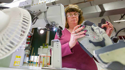 An employee prepares to stitch backtabs on a pair of New Balance shoes in Skowhegan, Maine.