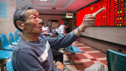 Investors observe stock prices at an exchange hall in Nanjing, China.