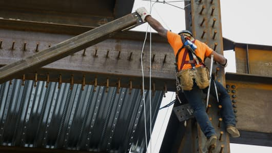 A contractor guides a steel beam into place while working on the Korean Air Wilshire Grand hotel and office building in downtown Los Angeles.