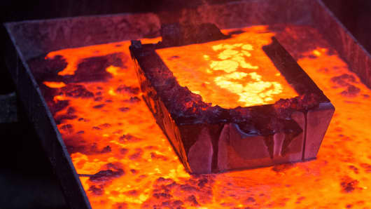 A casting mold filled with molten gold sits above a melting vat during the manufacture of gold ingots at the Suzdal gold mine, operated by Nordgold NV, in Semey, Kazakhstan.
