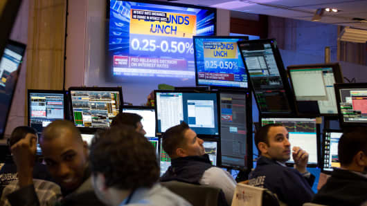 A television screen displays news about the U.S. Federal Reserve's announcement while traders work on the floor of the New York Stock Exchange (NYSE) in New York, U.S.