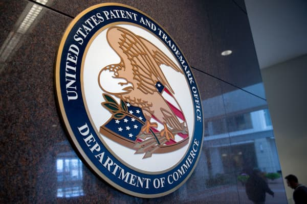 The U.S. Patent and Trademark Office seal is displayed inside the headquarters in Alexandria, Virginia.