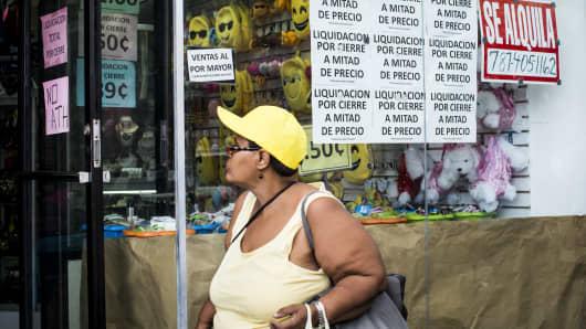 A pedestrian walks past a store that is under liquidation in the Rio Piedras neighborhood in San Juan, Puerto Rico