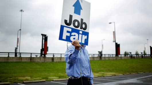 A Job News USA employee directs job seekers to a career fair at Papa John's Cardinal Stadium in Louisville, Kentucky.