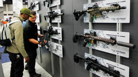 Gun enthusiasts view Sig Sauer rifles at the National Rifle Association's annual meetings & exhibits show in Louisville, Kentucky, on May 21, 2016.