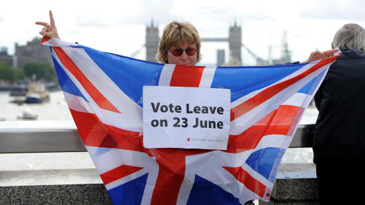 A leave supporter is seen as fishing boats campaigning for a Brexit sail down the Thames through central London.