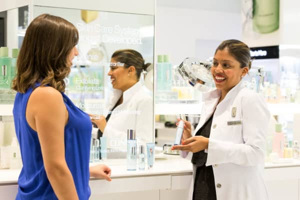 A Clinique consultant associate assists a client with make up products