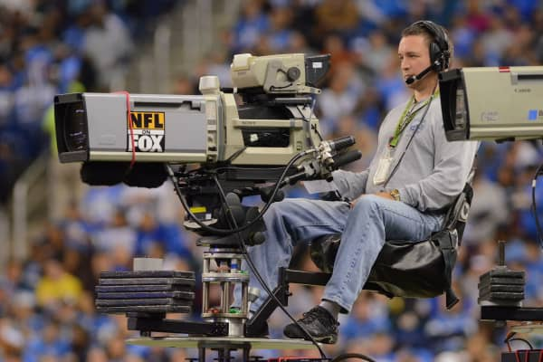 Fox camera operator sits above the crowd during a sports event.