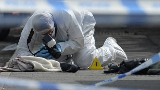 A police forensic officer works at the scene where a coat, shoe and handbag lie on the pavement outside the library in Birstall where Labour MP Jo Cox was shot on June 16, 2016.