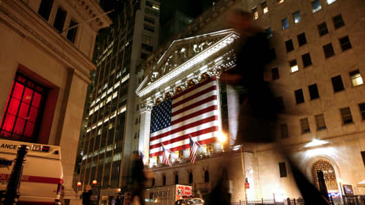 Pedestrians pass by the New York Stock Exchange, center, in downtown Manhattan, New York.