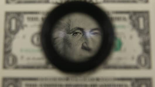 A magnifying glass is used to inspect newly printed one dollar bills at the Bureau of Engraving and Printing o