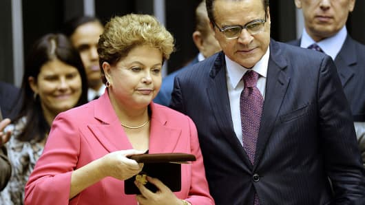 Brazilian Tourism Minister Luis Henrique Alves (R) with suspended President Dilma Rouseff (L) during a solemn session in Brasilia on October 9, 2013. Alves resigned on Thursday as the government of interim President Michel Temer lost its third minister in a month.