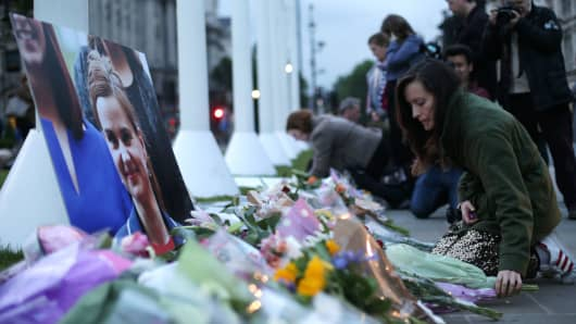 Floral tributes and candles are placed by a picture of slain Labour MP Jo Cox at a vigil in Parliament square in London on June 16, 2016. Cox died today after a shock daylight street attack, throwing campaigning for the referendum on Britain's membership of the European Union into disarray just a week before the crucial vote.