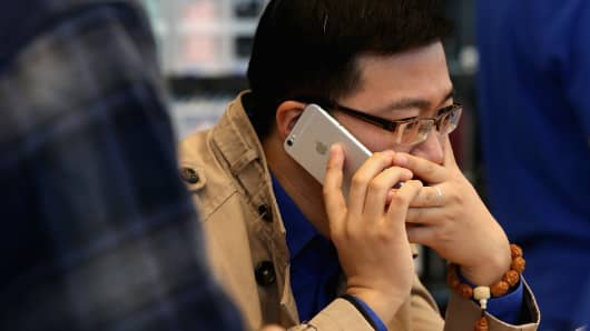 A Chinese man answers the phone with his new iPhone 6 Plus inside an Apple store in Beijing, China.