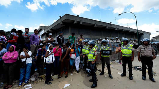 Police keep guard as people line up to buy groceries in a supermarket at Catia neighborhood in Caracas, on June 11, 2016.