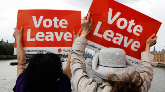 Leave the European Union campaigners wave banners near Parliament in London.