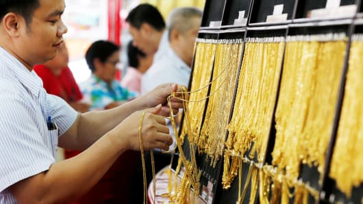 A salesman chooses gold chains for people buying gold in a jewelry store.