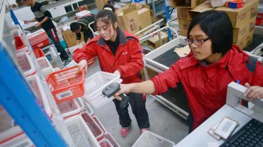 Workers at online marketplace JD.com checking goods on shelves at a warehouse in Langfang, China.