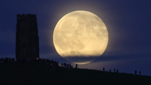 A full moon rises behind Glastonbury Tor as people gather to celebrate the summer solstice on June 20, 2016 in Somerset, England. Tonight's strawberry moon, a name given to the full moon in June by Native Americans because it marks the beginning of strawbe