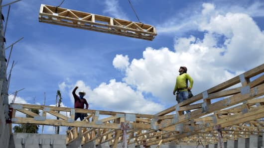 Construction workers set floor trusses in place that will support the second story of a home at the Lennar Corp. Madison Pointe at Central Park development in Doral, Florida.