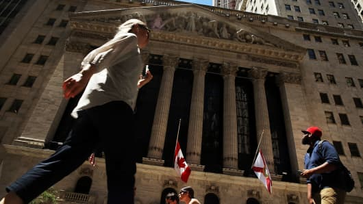 People walk by the New York Stock Exchange on June 15, 2016 in New York City.