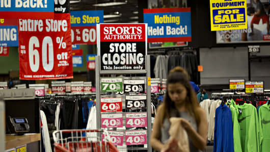 """A """"Store Closing"""" sign stands as a customer shops inside a Sports Authority store in Matteson, Illinois."""